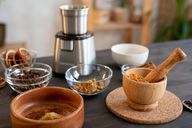 Group of bowls of various sizes with essential oils, coffee beans, dry flowers and other ingredients for making natural cosmetic products