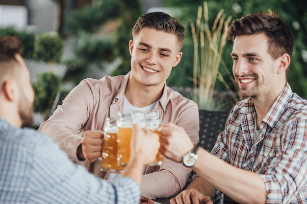 Group of boys cheering in cafe with beer