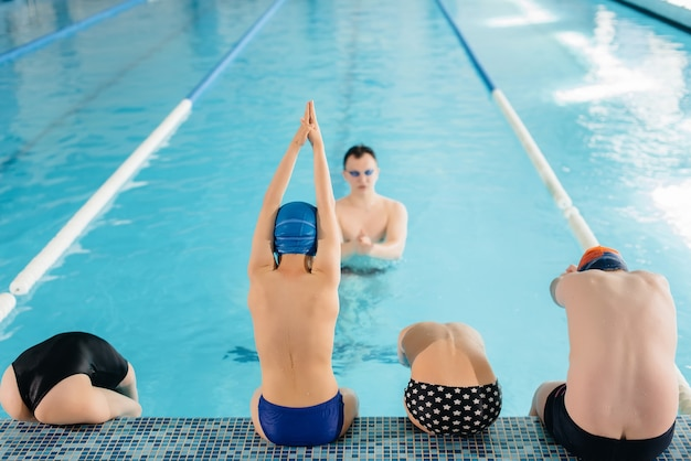 A group of boys and girls train and learn to swim in the pool with an instructor. development of children's sports.