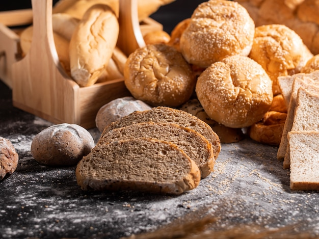 Group of bread on the black wooden table with sunlight