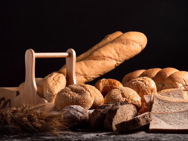 A group of bread on the wooden table and black