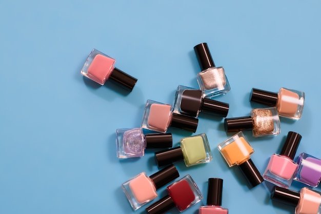 Group of bright nail polishes on blue surface. set of nail polish bottles top view.
