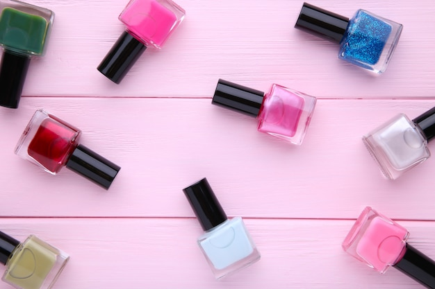 Group of bright nail polishes on pink background