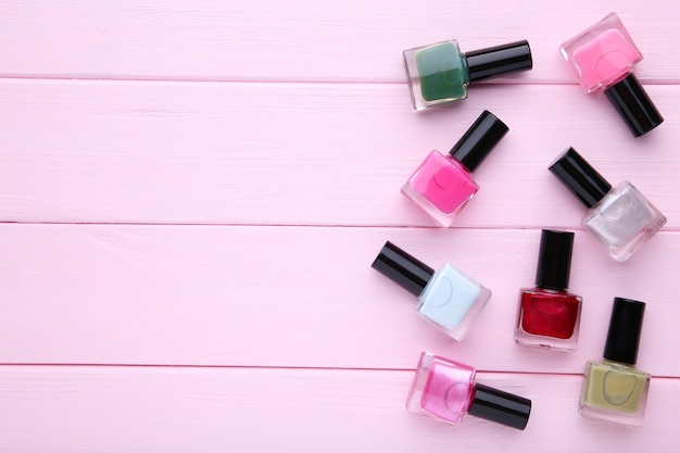 Group of bright nail polishes on pink