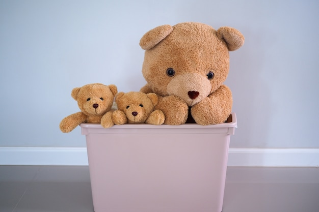 A group of brown-haired teddy bears in a pink box