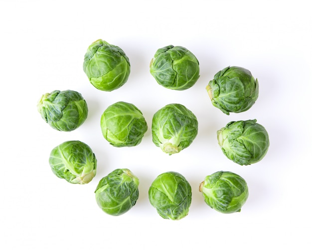 Group of brussel sprouts on white table.