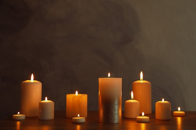 Group of burning candles on black table