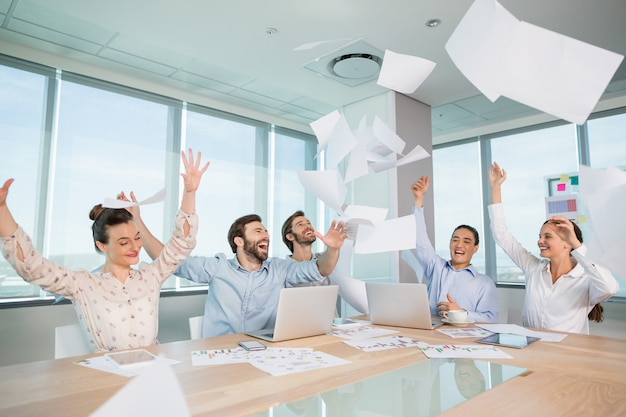 Group of business executives celebrating by throwing their business papers in the air