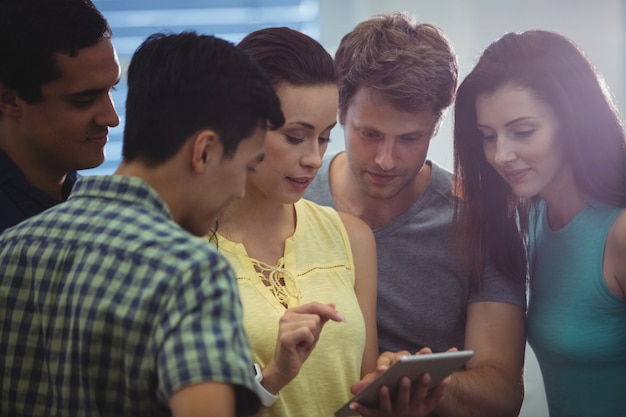 Group of business executives discussing over digital tablet