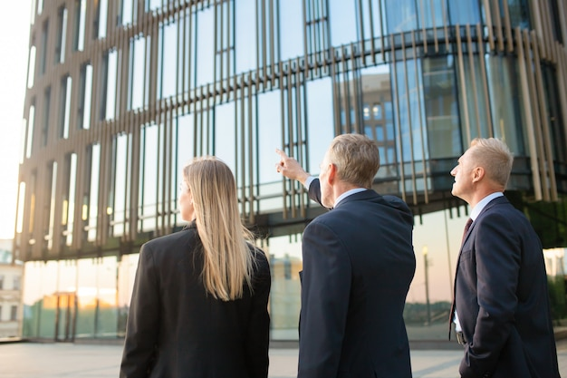 Group of business partners in formal suits pointing at office building, meeting outdoors, discussing real property. back view. commercial real estate concept