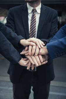 Group of business partners team with hands together