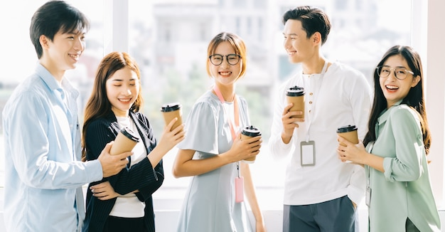 Group of business people are chatting and drinking coffee during recess