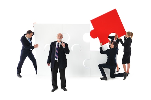 Group of business people assembling jigsaw puzzle isolated on white background