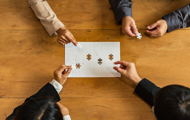 Group of business people assembling jigsaw puzzle and represent team support and help concept, busin