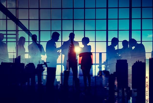Gruppo di gente di affari che fa brainstorming con il tramonto della siluetta
