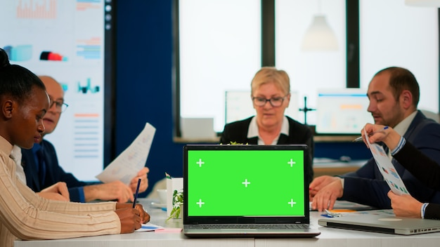 Group of business people discussing company plan with mockup laptop in front of camera, pc ready for financial project presentation placed on desk. leader using green screen pc with chroma key display