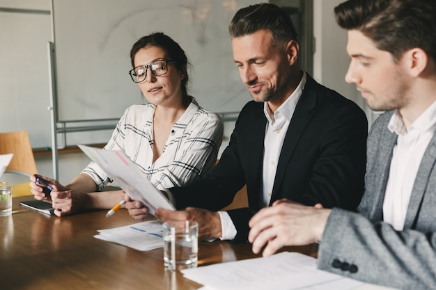 Group of business people in formal suits sitting at table in office, and examining resume of new personnel during job interview - business, career and placement concept