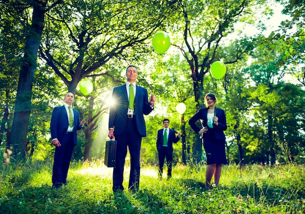 Group of business people holding balloons in the forest.