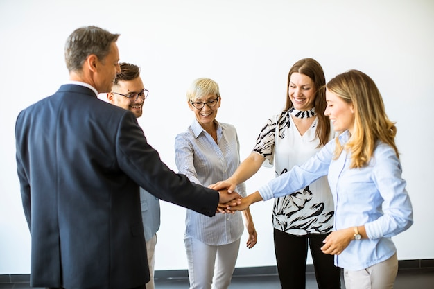 Group of business people holding hands together