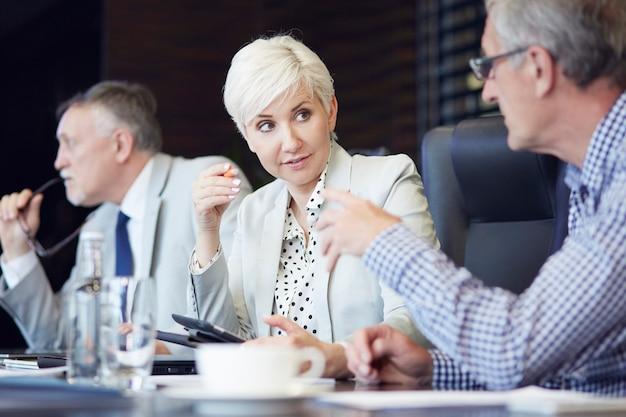 Gruppo di uomini d'affari accalcati intorno al tavolo a lavorare