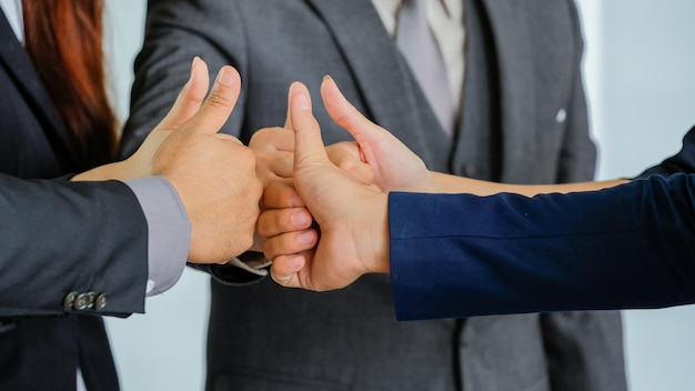 Group of business people meeting shaking hands together