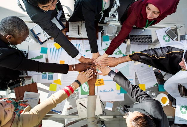 A group of business people putting hands together in a meeting