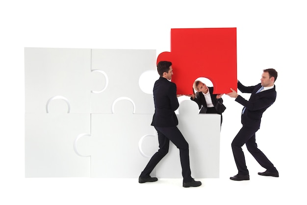 Group of business people putting new piece of jigsaw puzzle isolated on white background