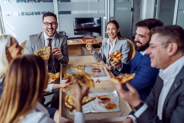 Group of business people sitting in boardroom, chatting, laughing and having pizza for lunch.