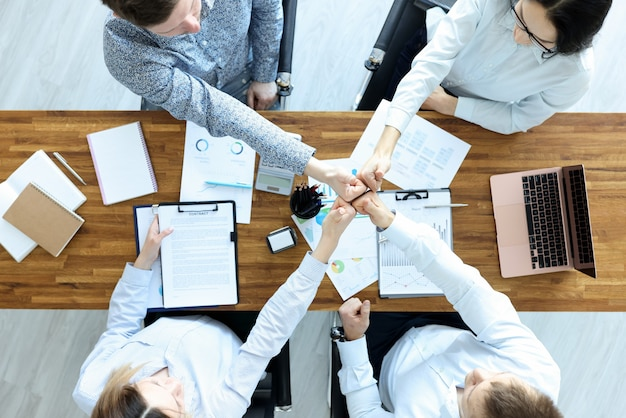 Group of business people sitting at table and showing thumbs up top view. successful business
