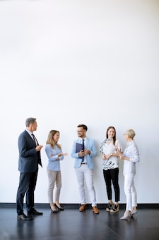 Group of business people standing by the wall in the office