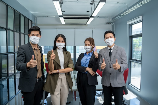 Group of business people wear mask for protect covid-19 have a meeting and talking in the office.