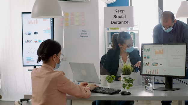 Group of business people with face masks working in new normal company office analysing financial project during coronavirus global pandemic. coworkers keeping social distancing to avoid virus disease
