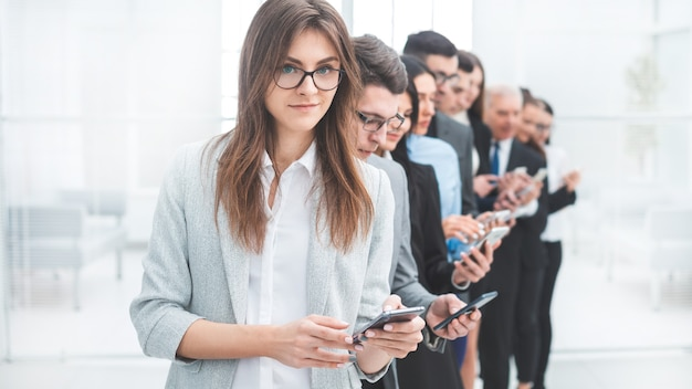 Group of business people with smartphones standing in a row