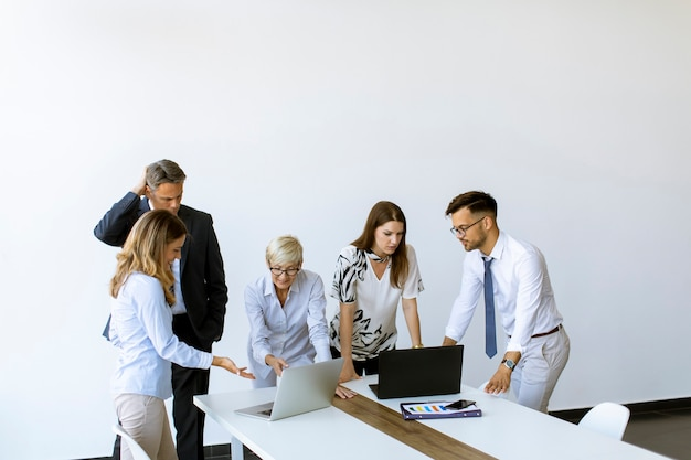 Group of business people with young adults and senior woman colleague on meeting at the modern bright office interior