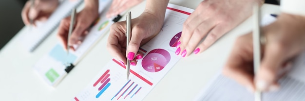 Group of business people writing with ballpoint pens in documents with graphs closeup