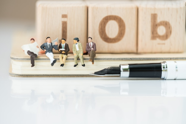 Group of business team sitting on notebook with pen and job word from wooden blocks.