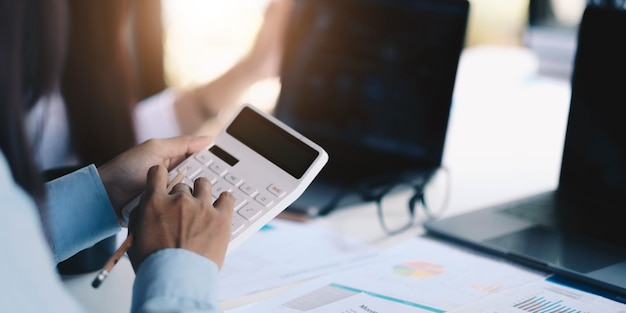 Group businessman hand using calculator calculating bonus(or other compensation) to employees to increase productivity.writing paper on desk.selective focus