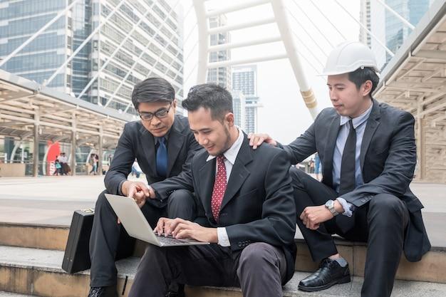 グループのビジネスマンが街でノートパソコンを使って相談する