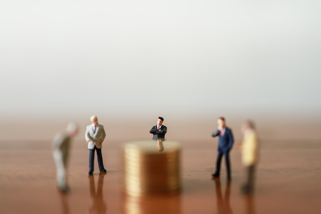 Group of businessman miniature figure people standing around stack of coins on wooden table.