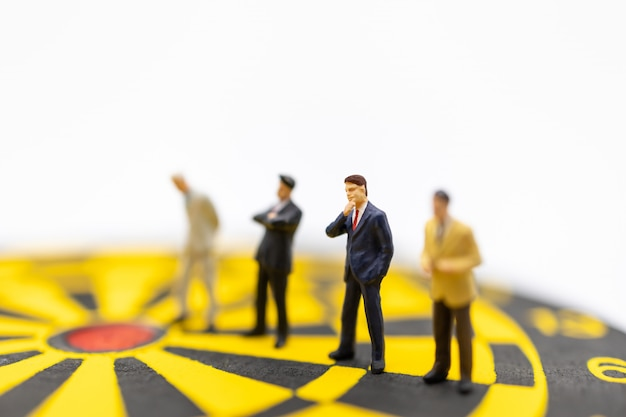 Group of businessman miniature figure standing on yellow and black dart board on white.
