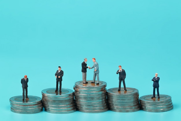 A group of businessman standing on coin stacking podium