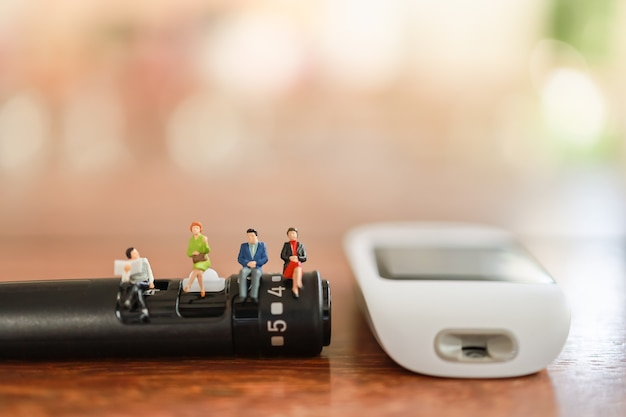 Group of businessman and woman miniature figure sitting on lancet with glucose meter
