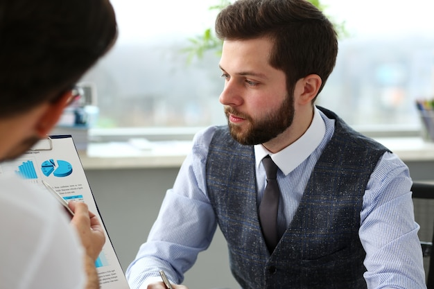 Group of businessmen with financial graph and silver pen in arm solve and discuss problem with colleague portrait. situation examination at board council sale adviser job stock exchange market profit