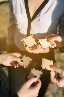 Group of businesspeople holding wooden jigsaw puzzle