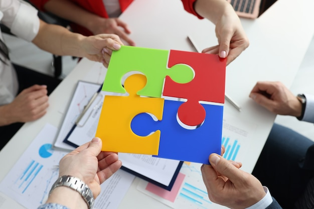 Group of businesspeople putting colorful puzzle over documents closeup