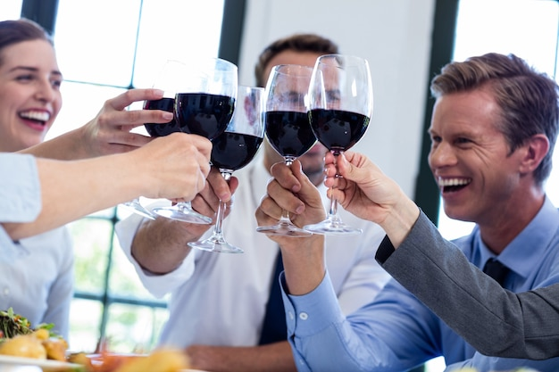 Group of businesspeople toasting wine glass during business lunch meeting
