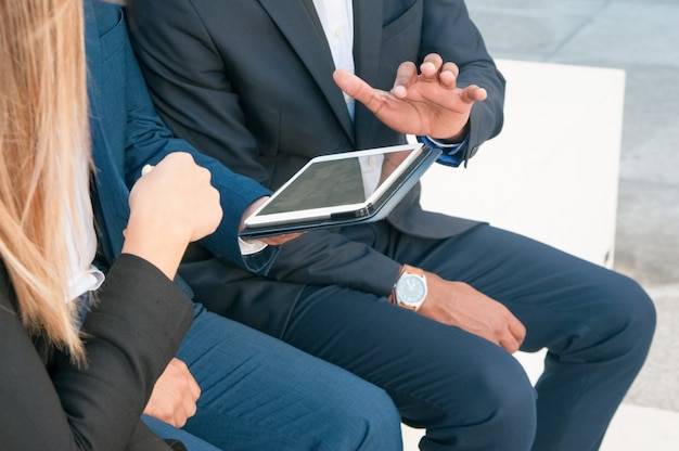 Group of businesspeople watching presentation on tablet
