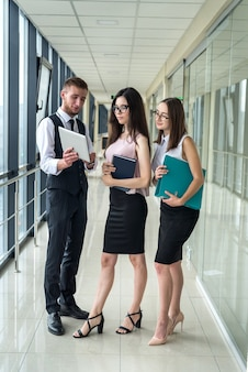 Group of businesspeople with paperwork on meeting before hard workday in office hall. teamwork