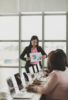 Group of businesswomen meeting together in office, leader or manager holding graph and chart while explaining details and meaning to audiences, the colleagues listen to her and express understanding.