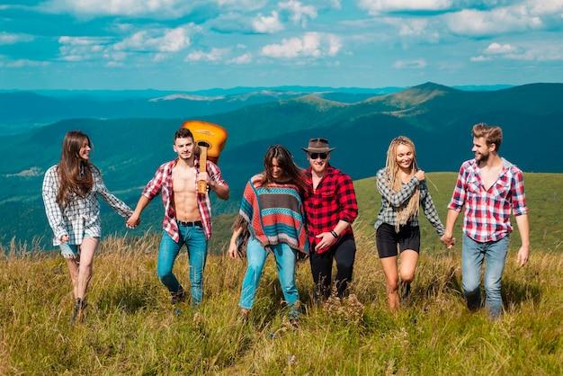 グループキャンプ。湖の近くを歩いているキャンプ旅行の友人、背面図。山の観光客。